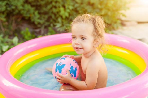 Children playing in inflatable baby pool.