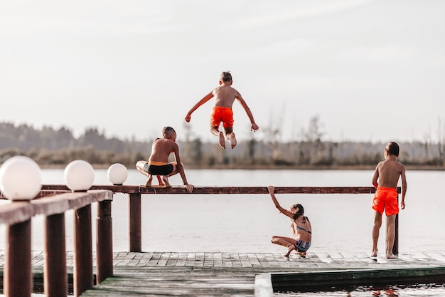 Children playing and  jumping into the water in swimsuits