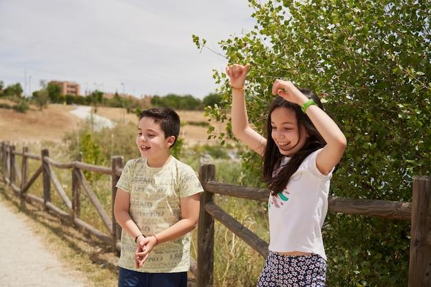後ろに木製の柵がある公園で楽しく笑っている子供たち
