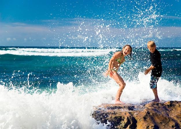 Children playing in ocean on rocks