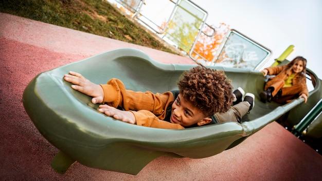 屋外で一緒にスライドで遊ぶ子供たち