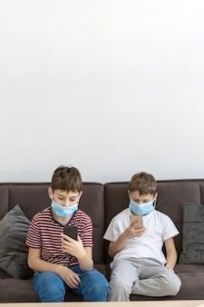 医療用マスクを着用しながらスマートフォンで遊ぶ子供たち