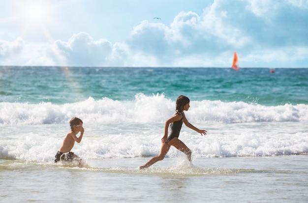 여름 방학에 해변에서 노는 아이들. 아름다운 바다, 모래, 푸른 하늘이 있는 자연 속의 소년 소녀. 물, 파도에서 실행 해변에서 휴가에 행복 한 아이. 조깅 훈련, 스포츠