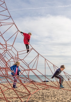 Children playing at the playground with ropes at the beach of barcelona, spain