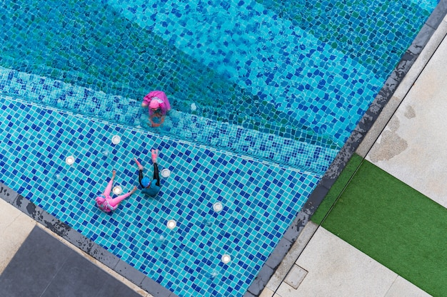 Children playing in the pool, aerial top view