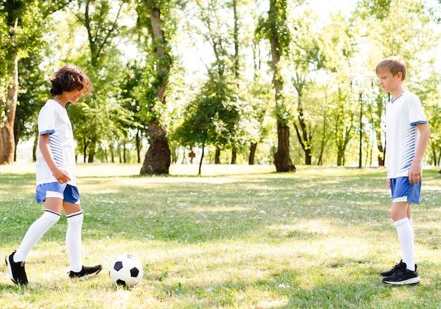 Дети вместе играют в футбол на улице