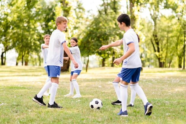 Bambini che giocano insieme a calcio