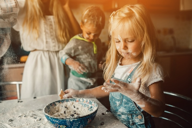 Children playing with a bowl of flour