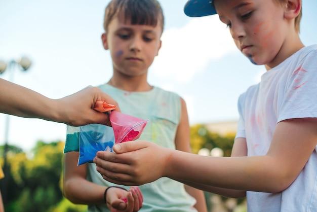 カラフルな粉で遊ぶ子供たち。ホーリー祭。ホーリー祭の間に楽しんでいる友達。幸せな子供時代。色で遊んでいる10代前の男の子。インドのお祭りホーリーのコンセプト。