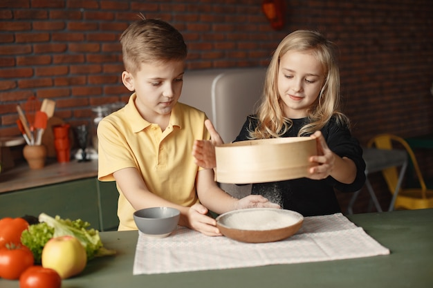 Children playing with a flour in a kitchen