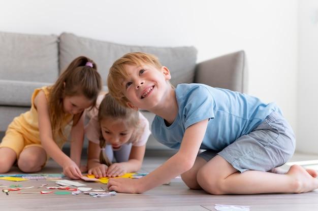 Дети играют с бумагой в полный рост