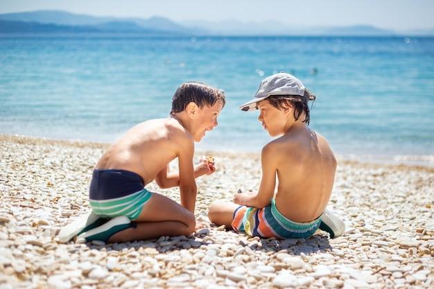 日当たりの良い海辺で小石で遊んでいる子供たち