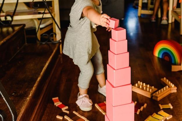 Дети, играющие с розовой башней в классе монтессори