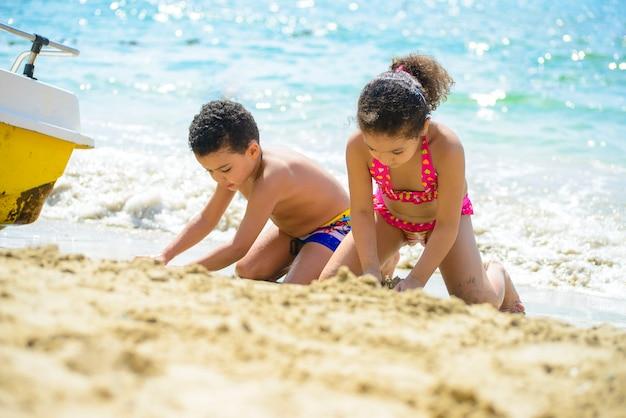 海の海岸で砂で遊んでいる子供たち
