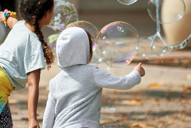 Bambini che giocano con le bolle di sapone