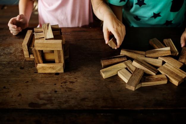 Дети играют в игрушку из деревянных блоков с учителем