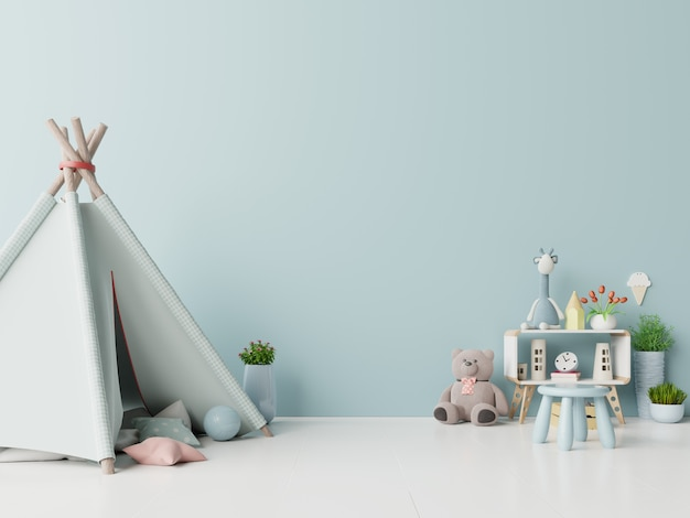 Children playroom with tent and table sitting doll on empty blue wall background.
