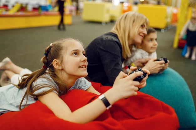 Дети играют в игровую приставку, развлекательный центр