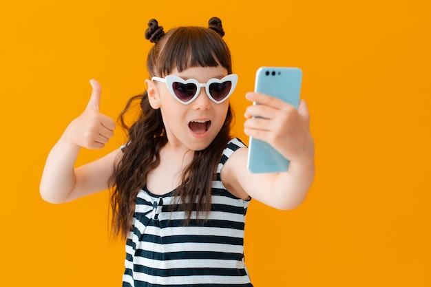それのように、孤立した黄色の壁にスマートフォンを持ったかわいい女の子の子供の肖像画。子供は感情的な楽しい自分撮りをクールにし、親指を立てます。子供のブロガー、ガジェット、インターネット