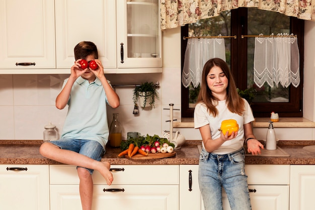 Children posing with vegetables in the kitchen