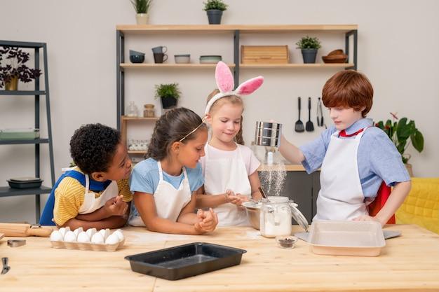 一緒に生地を注いでいる子供たち、両親のために食欲をそそるクッキーを準備している間、広い笑顔でお互いを見つめているエプロンを着ています