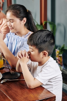 Children praying before dinner