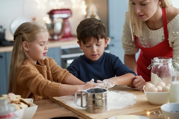 クリスマスのクッキーのためにペストリーを準備している子供たち