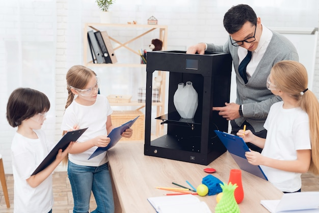 Children print different items on 3d printer with a teacher.