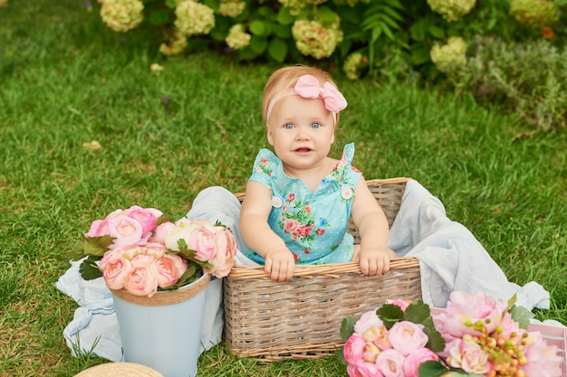 Children protection day, baby girl in the park sits in a basket on a summer picnic