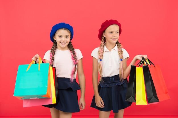 빨간색 배경 쇼핑에 만족한 어린이 학생. 쇼핑과 의류 쇼핑몰에 사로잡혀 있습니다. 쇼핑 중독 개념입니다. 당신이 쇼핑에 중독되었다는 신호. 아이들은 귀여운 여학생들이 쇼핑백을 들고 있습니다.