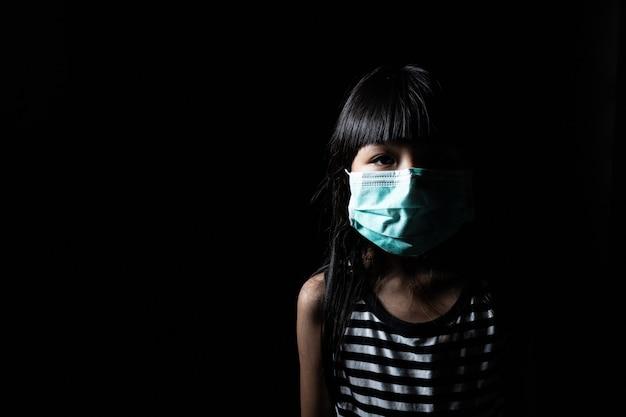 子供たちはマウスマスクを着用して、covid-19やコロナウイルスなどのさまざまなウイルスが黒いシーンで体内に侵入するのを防ぎました。