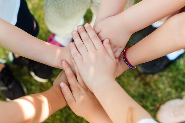 Дети складывают руки на открытом воздухе, вид сверху. группа молодых людей руками. концепция команды, совместной работы, единства и дружбы.