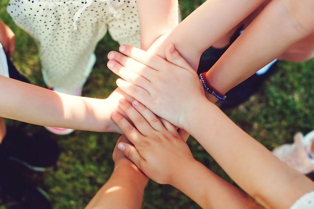 야외에서 손을 모은 아이들, 최고 전망. 젊은 사람들의 손의 그룹입니다. 팀, 팀워크, 화합 및 우정 개념.