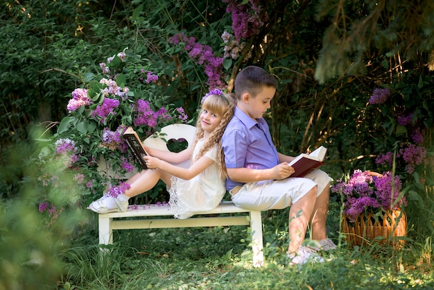 Children read books in lilacs.