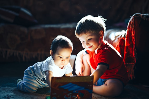 Children reading a book sitting together on floor at home.