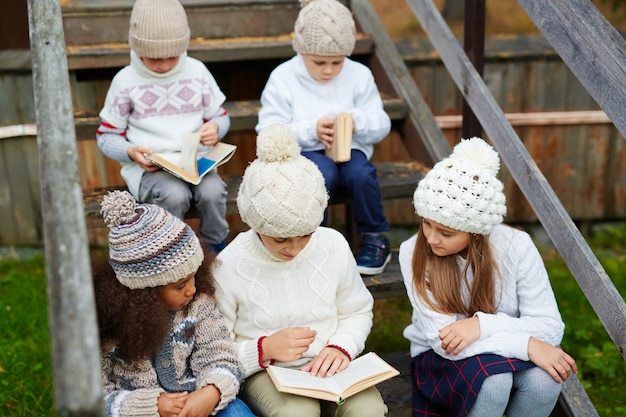 Children reading books outdoors