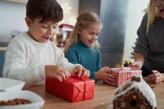 母親からクリスマスプレゼントを受け取る子供たち