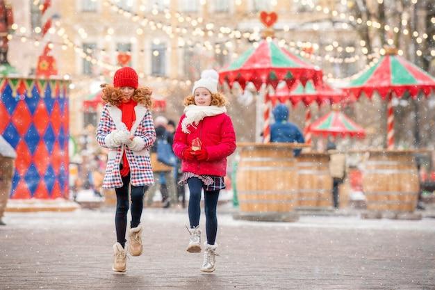 赤毛の姉妹である子供たちは、街のお祝いに飾られたクリスマスマーケットで、買い物用のおもちゃを手に持って歩きます。