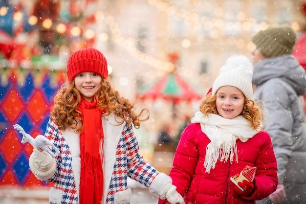 Дети, рыжеволосые сестры, гуляют вместе с игрушками в руках на празднично украшенной рождественской ярмарке в городе.