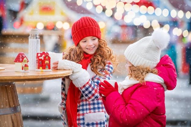子供たち、赤毛の姉妹は、街のお祝いに飾られたクリスマスマーケットで、熱いお茶のマグカップで手袋をはめた手を温めます。