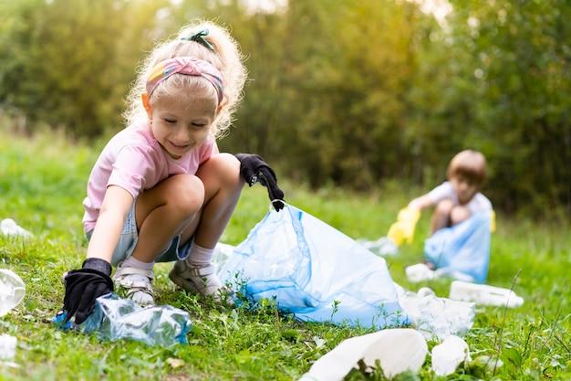 아이들은 플라스틱 쓰레기를 제거하고 야외에서 생분해성 쓰레기 봉투에 넣습니다. 생태, 폐기물 처리 및 자연 보호의 개념. 환경 보호.