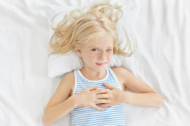 子供、残り、人々の概念。長いブロンドの髪を持つ素敵な女の子、寝たいと思っている間片目を閉じ、白いベッドに横たわって寝ます。自宅の寝室で休んでそばかすのある少女