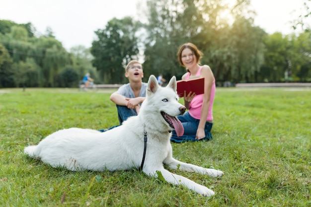 Children rest in the park with a dog