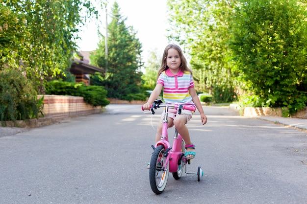 Children ride a bike near the house.