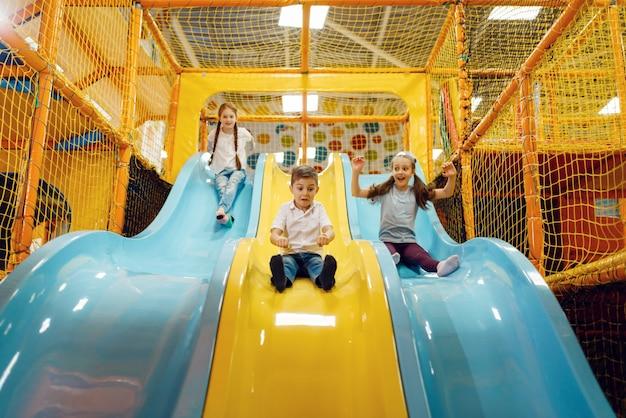 아이들은 엔터테인먼트 센터의 언덕을 타고 내려갑니다. 휴일에 소녀와 소년 여가, 어린 시절의 행복, 놀이터에서 행복한 아이들