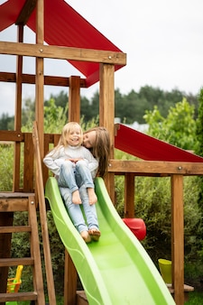 Children ride from the children's slide, sisters play together in the garden