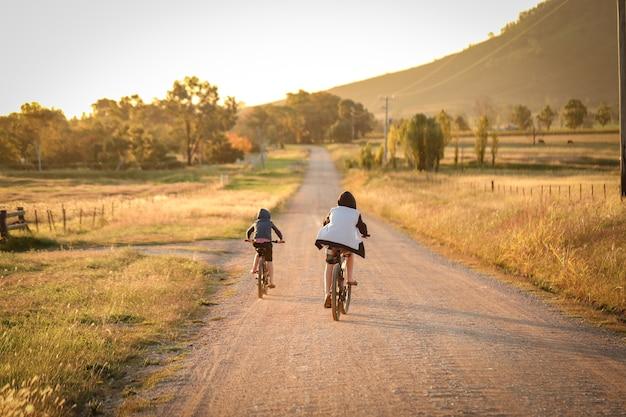 遠く離れた田舎道で自転車に乗る子供たち