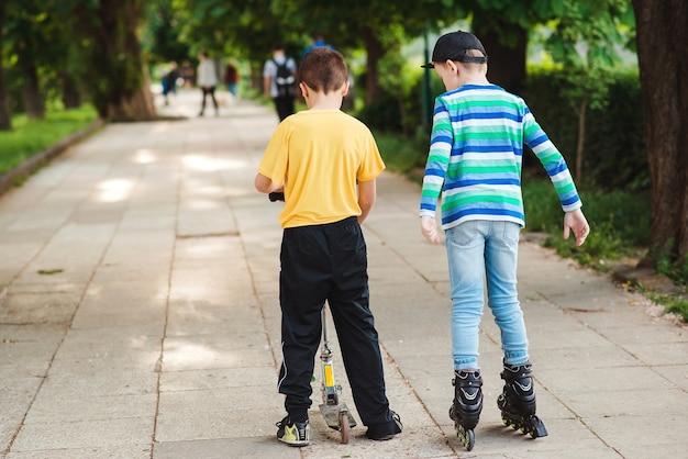 거리에서 스쿠터와 롤러 스케이트를 타는 아이들. 밖에서 함께 시간을 보내는 친구들의 뒷모습. 아이들을 위한 활동적인 야외 스포츠