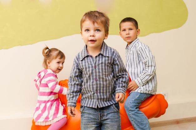 Children on the rocking plastic seesaw in the room indoor