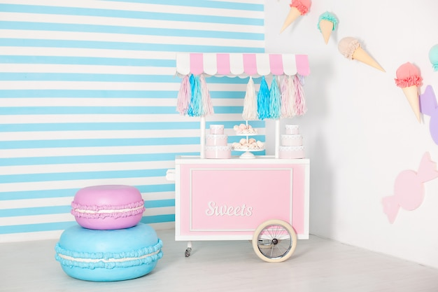 Children room with blue stripe wall. candy stall photo zone with big macaroons, sweets and marshmallows. trolley with ice cream.  decorated room for a birthday. cart with candy bar.